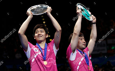 South Korea's Jae Sung Jung, right, and Yong Dae Lee hold their trophies as they celebrate their men's doubles final victory against China's Yun Cai and Haifeng Fu at The All England Open Badminton Championships, in Birmingham, England