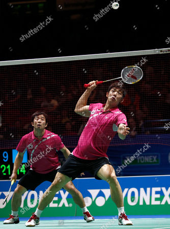 South Korea's Yong Dae Lee, right, prepares to smash as partner Jae Sung Jung looks on and during their men's doubles final against China's Yun Cai and Haifeng Fu at The All England Open Badminton Championships, Birmingham, England