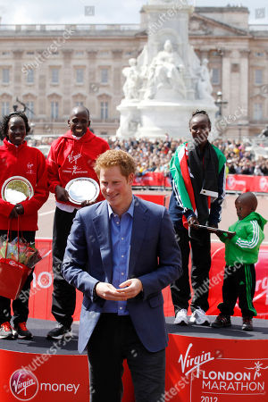 Stock Photo of Prince Harry, Mary Keitany Backdropped by Buckingham Palace, Britain's Prince Harry, center, reacts after presenting the trophy to London Marathon's women's winner Kenya's Mary Keitany with her son Gerard, right, as second place men Kenya's Martin Lel, second left, and second place women Kenya's Edna Kiplagat, left, look on during the trophy presentation, London