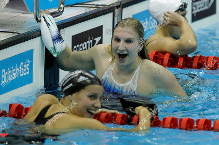 Olympic double gold medalist Britain's Rebecca Adlington, center, celebrates winning gold with silver medalist Joanne Jackson, left, after the final of the women's 400m freestyle during the British Swimming Championship selection trials and Olympic test event at the London 2012 Olympic Aquatics Centre at the Olympic Park in London, . A number of international swimmers have been invited to attend the championships and compete in guest finals