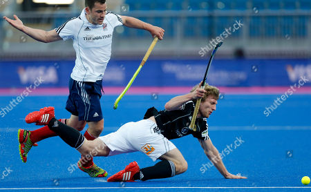 Britain's James Tindall, left, competes for the ball with Germany's Jan Philipp Rabente during the men's preliminary round field hockey match between Britain and Germany at the Riverbank field hockey arena in the Olympic Park in London