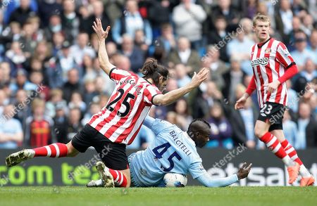 Manchester City's Mario Balotelli, centre, is felled by Sunderland's Sotirios Kyrgiakos during their English Premier League soccer match at The Etihad Stadium, Manchester, England