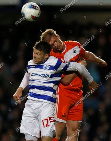 QPR's Jamie Mackie, left, jumps for the ball with Swansea's Alan Tate during the English Premier League soccer match between Queen's Park Rangers and Swansea City at Loftus Road Stadium in London