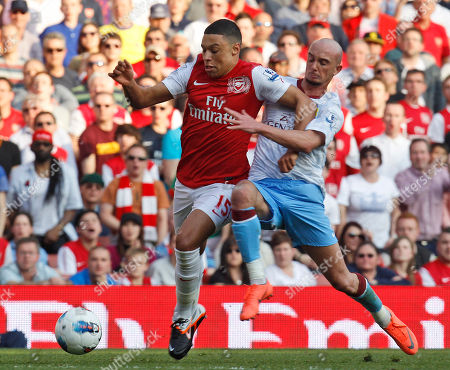 Stock Photo of Arsenal's Alex Chamberlain, left, tries to control the ball past Aston Villa's Stephen Ireland during an English Premier League soccer match at the Emirates Stadium in London, . Arsenal won the match 3-0