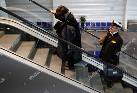 James Allan Flood a marine artist from Del Ray Beach in Florida is seen on an escalator as he arrive to check in for the MS Balmoral Titanic memorial cruise, in Southampton, England, . Nearly 100 years after the Titanic went down, a cruise with the same number of passengers aboard is setting sail to retrace the ship's voyage, including a visit to the location where it sank. The Titanic Memorial Cruise is set to depart Sunday from Southampton, where the Titanic left on its maiden voyage. The 12-night cruise will commemorate the 100th anniversary of the sinking of the White Star liner. With 1,309 passengers aboard, the MS Balmoral will follow the same route as the Titanic. Organizers are trying to recreate the onboard experience minus the disaster from the food to a band playing music from that era.Organizers said people from 28 countries have booked passage, including relatives of some of the more than 1,500 people who died when the Titanic collided with an iceberg and sank on April 15, 1912