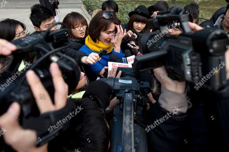 "Kim Lee ADVANCE FOR USE AND THEREAFTER - In this Thursday, March 22, 2012 photo, Kim Lee, center, wife of ""Crazy English"" founder Li Yang, is surrounded by local journalists as she leaves a court building after a session for her divorce trial in Beijing, China. Lee's case has opened the door to a torrent of anguish about domestic violence in her adopted country and she has became a folk hero for battered Chinese women. In China, where tradition holds that family matters are private and women are in many ways subservient to their husbands, the American woman's case has spawned tens of thousands of postings on Twitter-like sites, along with protests and talk show debates. It is especially explosive because she is a foreigner, at a time when China is particularly sensitive about how it is understood and treated by the world"