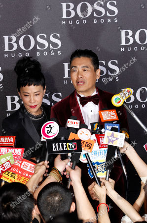 Hong Kong actor Chow Yun Fat, right, speaks near his wife Jasmine Tan at left to journalists gathered at the Hugo Boss Black Fashion Show held in Beijing, China