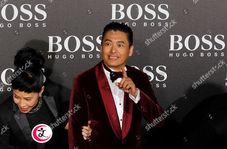 Stock Photo of Hong Kong actor Chow Yun Fat, center, gestures near his wife Jasmine Tan as they talk to journalists at the Hugo Boss Black Fashion Show held in Beijing, China