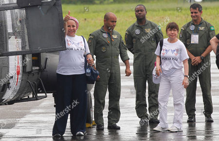Former Colombian senator Piedad Cordoba, left, flashes a thumbs up sign next to crew members of a Brazilian army helicopter, upon her arrival to attend to the release of the last group of soldiers and police held by Colombia's main rebel group, in Villavicencio, Colombia, . The leftist Revolutionary Armed Forces of Colombia, known as the FARC, has promised to free the 10 captives, likely in several stages. All have been held for at least 12 years. Pictured second from right is Olga Amparo Sanchez member of the Colombians for Peace group