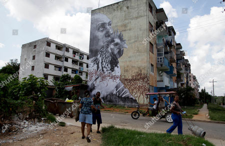 """People walk in front of an installation by Cuban-American artist Jose Parla titled """"Wrinkles of The City"""" as part of the 11th Havana Biennial contemporary art exhibition in Havana, Cuba"""