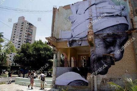 "People walk near an installation by Cuban-American artist Jose Parla titled ""Wrinkles of The City"" as part of the 11th Havana Biennial contemporary art exhibition in Havana, Cuba"