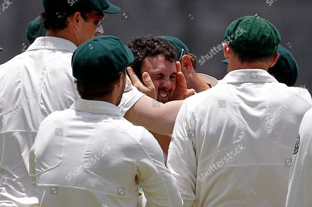 Australia's Ed Cowan, center, is congratulated by teammates after taking the catch to dismiss West Indies' opener Adrian Barath for a duck during the second innings on the fourth day of their third and final cricket Test match in Roseau, Dominica