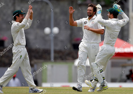 Australia's Ed Cowan, left, celebrates with bowler Ben Hilfenhaus, center, and wicket keeper Matthew Wade after taking the catch to dismiss West Indies' opener Adrian Barath for a duck during the second innings on the fourth day of their third and final cricket Test match in Roseau, Dominica