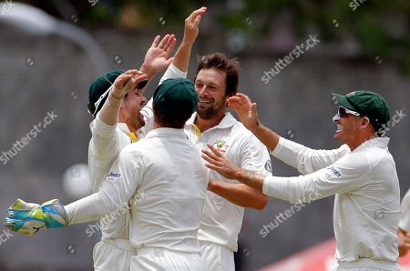 Australia's Ed Cowan, left, celebrates with bowler Ben Hilfenhaus, center right, Mike Hussey, right, and wicket keeper Matthew Wade after taking the catch to dismiss West Indies' opener Adrian Barath for a duck during the second innings on the fourth day of their third and final cricket Test match in Roseau, Dominica
