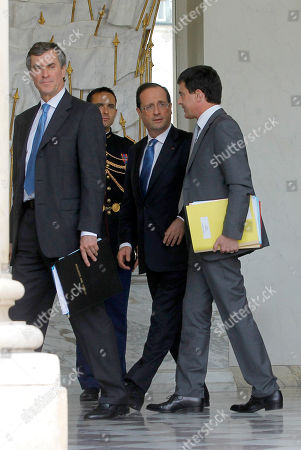 French President Francois Hollande, center, Interior Minister Manuel Vals, right, and Budget Minister Jerome Cahuzac, left, walk after a weekly cabinet meeting in Elysee Palace, Paris