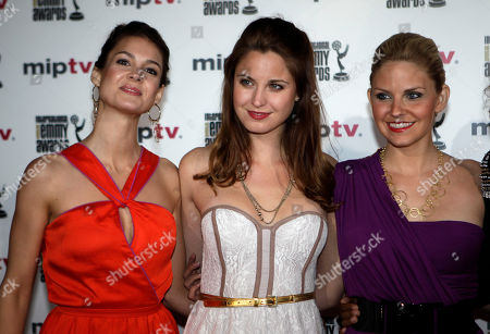 """Left to right, US actresses,Tiffany Brouwer, Christine Donion and Nikki Griffin, pose for photographers as they launch """"Femme Fatales """" during the MIPTV, International Television Programme Market, in Cannes, southern France. Femme Fatales is a sexy, thrilling anthology series about powerful, sexy and dangerous women inspired by and styled in the tradition of pulp stories, film noir and graphic novels"""