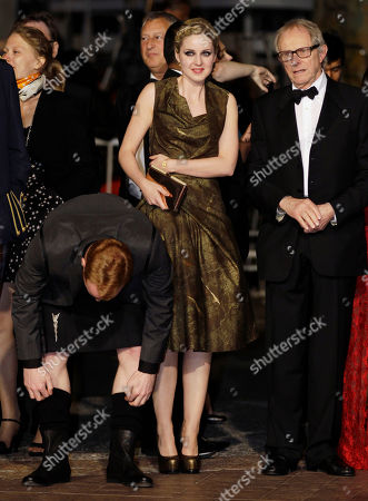 Siobhan Reilly, Ken Loach, William Ruane Actor William Ruane, left, adjusts his socks, while actress Siobhan Reilly, center, and director Ken Loach prepare to walk the red carpet as they arrive for the screening of The Angel's Share at the 65th international film festival, in Cannes, southern France
