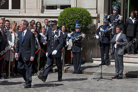 France's new Interior Minister Manuel Valls, right, looks on as outgoing interior minister Claude Gueant, left, walks away during the handover ceremony, in Paris
