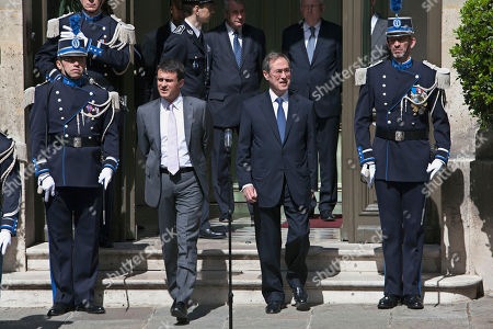 France's new Interior Minister Manuel Valls, center left, and outgoing interior minister Claude Gueant, center right, arrive to make a speech during the handover ceremony, in Paris