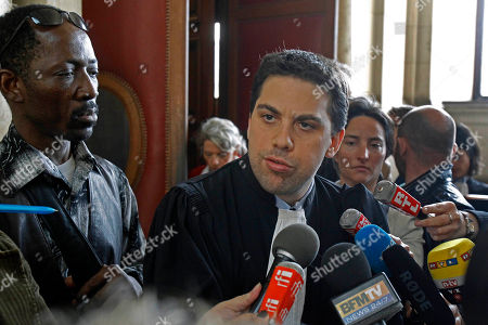 SOS Racism movement lawyer Patrick Klugman addresses reporters at Paris Court House, after French court convicted longtime perfume maker Jean-Paul Guerlain of making racist insults on national television and fined him Thursday Euros 6,000 ($8,000). The 75-year-old Guerlain, an heir to his family's cosmetics empire, provoked anger among French minorities with the comments in a 2010 interview on France-2 television. Lawyers for the SOS Racism association said Guerlain abused the national platform he was given. Man at left is unidentified