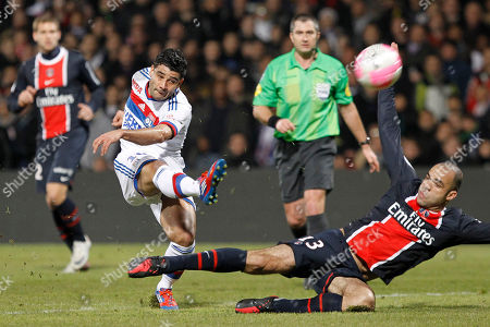 Lyon's Ederson, left, is tackled by Paris Saint Germain's Alex Rodrigo Dias Da Costa, right, as he kicks the ball during their French League One soccer match at Gerland stadium, in Lyon, central France