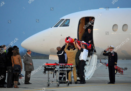 Firefighters and medics carry French wounded journalist Edith Bouvier out of the plane carrying her and French photographer, William Daniels, after they landed at the Villacoublay military airport outside Paris, . Two French journalists who were smuggled out of Syria have arrived in France. Edith Bouvier, who was injured, and William Daniels were caught up in a Syrian government siege of a rebel-held neighborhood in the city of Homs