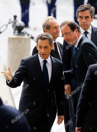 Francois Hollande, Nicolas Sarkozy Outgoing French President Nicolas Sarkozy, left, gestures to President-elect Francois Hollande, second right, during commemorations at the Arc de Triomphe, in Paris, marking the anniversary of the end of World War II in Europe. French Defense Minister Gerard Longuet, at second left, and Prime Minister Francois Fillon, at right