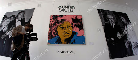 A TV woman films in front of a portrait of German artist and celebrity Gunter Sachs by Andy Warhol during a Sotheby's exhibition preview in Munich, Germany, . The auction will be held at Sotheby's in London on May 22-23
