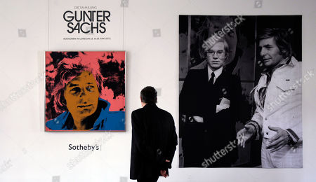 A man walks in front of a portrait of German artist and celebrity Gunter Sachs by Andy Warhol during a Sotheby's exhibition preview in Munich, Germany, . The auction will be held at Sotheby's in London on May 22-23