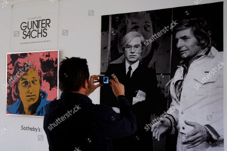A man takes pictures in front of a portrait of German artist and celebrity Gunter Sachs by Andy Warhol during a Sotheby's exhibition preview in Munich, Germany, . The auction will be held at Sotheby's in London on May 22-23