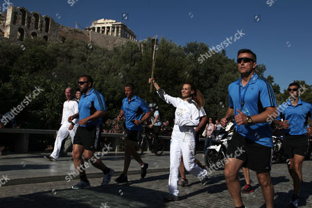 Stock Photo of Artemis Ignadiou Artemis Ignadiou, center, choreographer of the Olympic flame ceremony in ancient Olympia, carries the torch past the ancient Parthenon temple in Athens, . The Olympic flame will travel to London, where the Summer Games will take place from July 27-Aug. 12