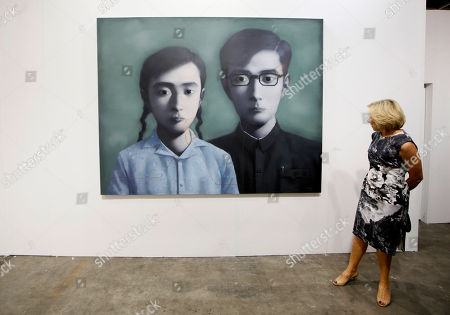 """A woman looks at a painting titled """"Brother and Sister"""" created by Chinese artist Zhang Xiaogang at the Art HK 12 art fair in Hong Kong . ART HK 12 is a fair showcasing artwork for sale from 266 galleries representing 39 international territories"""
