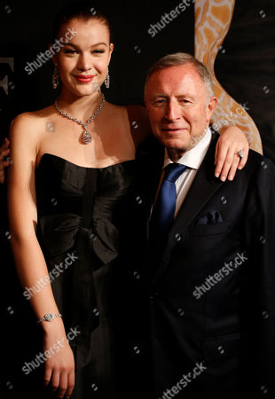 """Founder and Chairman of Graff Diamonds Laurence Graff, right, poses with a model who is wearing a 100 carats diamond named """"The Flame"""" before attending the IPO roadshow in Hong Kong . British jeweler Graff Diamonds posted a so-called """"red herring"""" prospectus on the Hong Kong stock exchange website over the weekend as it prepares to hold an initial public offering, becoming the latest foreign luxury brand company to targeting growth in China"""