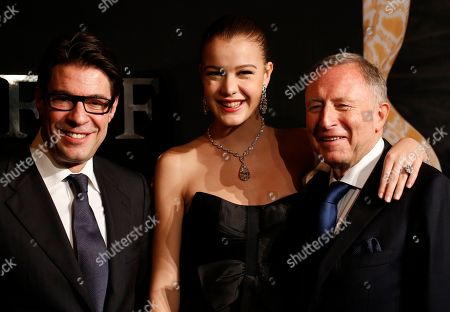 """Founder and Chairman of Graff Diamonds Laurence Graff, right, and CEO Francois Graff, left, pose with a model who is wearing a 100 carats diamond named """"The Flame"""" before attending the IPO roadshow in Hong Kong . British jeweler Graff Diamonds posted a so-called """"red herring"""" prospectus on the Hong Kong stock exchange website over the weekend as it prepares to hold an initial public offering, becoming the latest foreign luxury brand company to targeting growth in China"""