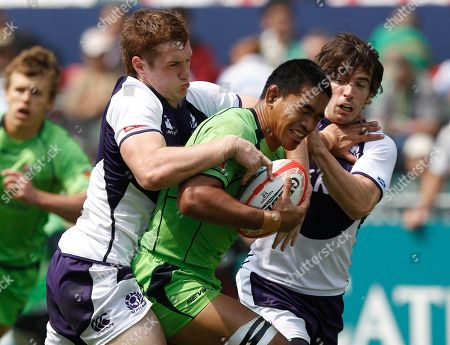 Jordan Tuapou, Michael Fedo, Colin Gregor Jordan Tuapou of Australia, center, is tackled by Michael Fedo, left, and Colin Gregor of Scotland during their second day match of the Hong Kong Sevens rugby tournament in Hong Kong, . Australia won 29 to 14