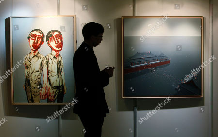 "A man walks past paintings titled ""Flooding the Forbidden City No.10"", right, by Chinese artist Chen Lianqing and ""Two Men (from Mask Series)"" by Chinese artist Zeng Fanzhi at the Seoul Auction in Hong Kong . Auctioneers in Hong Kong have sold 10 paintings seized from a South Korean bank that collapsed last year amid a corruption scandal to raise $2.4 million to help repay depositors. The paintings included works by noted Chinese artists Zeng and Zhang Xiaogang and American Julian Schnabel"
