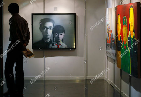 "A man walks past a painting titled ""Bloodline Series"", center, by Chinese artist Zhang Xiaogang at the Seoul Auction in Hong Kong . Auctioneers in Hong Kong have sold 10 paintings seized from a South Korean bank that collapsed last year amid a corruption scandal to raise $2.4 million to help repay depositors. The paintings included works by noted Chinese artists Zeng Fanzhi and Zhang Xiaogang and American Julian Schnabel"