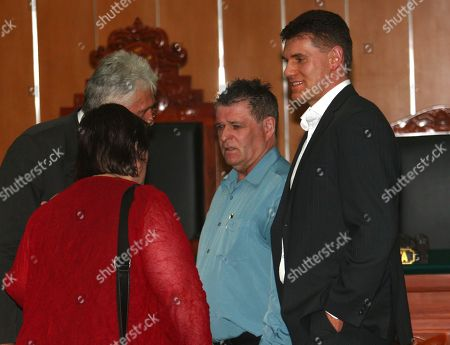 Australian survivors of 2002 Bali bombings Jason McCartney, right, and Peter Hughes, second right, talk to unidentified embassy officials before testifying against Indonesian militant Umar Patek in his trial at West Jakarta district court in Jakarta, Indonesia, . Patek is accused of building the massive bomb used in the deadly attacks on the resort island