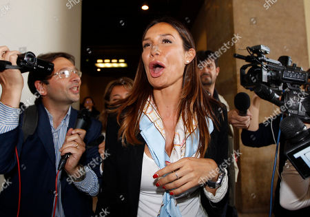 """Italian People for Freedom party local politician and former showgirl Nicole Minetti, leaves a court room during a break of a trial in Milan's court, Italy, . Minetti, along with other two ex-Italian Premier Silvio Berlusconi aides, Emilio Fede, an executive in Berlusconi's media empire, and talent agent Dario """"Lele"""" Mora, has gone on trial on charges for allegedly recruiting an underage Moroccan girl and other women for prostitution at Berlusconi's villas. Berlusconi is being tried separately for allegedly paying for sex with the Moroccan girl, charges he denies"""