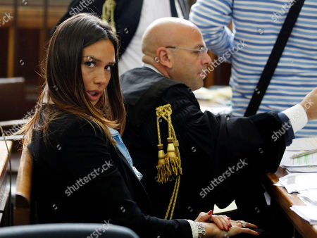 """Italian People for Freedom party local politician and former showgirl Nicole Minetti looks on during a break of a trial in Milan's court, Italy, . Minetti, along with other two ex-Italian Premier Silvio Berlusconi aides, Emilio Fede, an executive in Berlusconi's media empire, and talent agent Dario """"Lele"""" Mora, has gone on trial on charges for allegedly recruiting an underage Moroccan girl and other women for prostitution at Berlusconi's villas. Berlusconi is being tried separately for allegedly paying for sex with the Moroccan girl, charges he denies"""