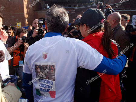 """Rome's mayor Gianni Alemanno, left, holds Lazio region president Renata Polverini, as he wears a t-shirt showing the two Italian marine security guards arrested in India prior to the start of the Roma City Marathon in Rome, . The two marine guards were arrested in Kochi, India, for allegedly shooting to death two Indian fishermen they mistook for pirates. The Italian writing reads"""" Let's save our Marines"""