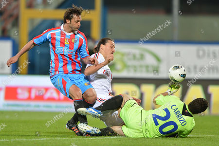 Catania defender Nicola Legrottaglie, left, AC Milan forward Zlatan Ibrahimovic, of Sweden, center, and Catania goalkeeper Juan Pablo Carrizo, of Argentina, fight for the ball during Serie A soccer match between Catania and AC Milan at the Angelo Massimino stadium in Catania, Italy