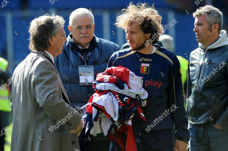 """Genoa's Marco Rossi talks to president Enrico Preziosi as he holds teammates' jerseys as the Serie A soccer match between Genoa and Siena was suspended at Genoa's Luigi Ferraris stadium, Italy, . Fan protests prompted Siena's 4-1 win at Genoa to be suspended for about 45 minutes Sunday with Siena leading 4-0 early in the second half. Genoa fans threw flares onto the pitch and climbed atop barriers as they were faced by stewards in riot gear. One section of hard-core """"ultra"""" fans got up and walked out of the Luigi Ferraris stadium. Genoa captain Marco Rossi spoke with the fans at one point and he then removed his jersey and also gathered teammates' jerseys"""