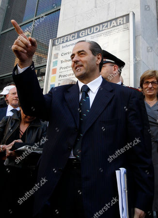 Former PM and Italia dei Valori leader Antonio Di Pietro gestures as he meets the press outside the tribunal after giving his testimony in a process where Silvio and his brother Paolo Berlusconi are accused, in Milan, Italy