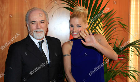 Italian showgirl Michelle Hunzinker flanked by Itlian TV director Antonio Ricci attend the journalism prize event 'E' Giornalismo' in Milan, Italy, Thursday, March, 22, 2012