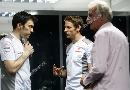 Stock Image of F1autoz12 McLaren Formula One driver Jenson Button, centre, of Britain talks with a teammate as his father John Button right, looks on after the Malaysian Formula One Grand Prix at Sepang, Malaysia
