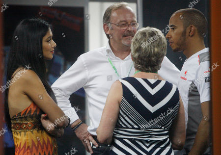 Stock Picture of F1autoz12 McLaren Formula One driver Lewis Hamilton,right, of Britain talks with his girlfriend Nicole Scherzinger left, his manager Didier Coton, second left, and his mother Brenda Lockhart following his third place finsih at the Malaysian Formula One Grand Prix at Sepang, Malaysia