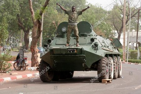 A soldier poses atop a military vehicle, as it stands guard outside the presidential palace following a military coup in Bamako, Mali, . The whereabouts of Mali's president Amadou Toumani Toure were unknown Friday, a day after mutinous soldiers declared a coup, raising fears and prompting uncertainty in a West African nation that had been one of the region's few established democracies