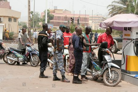 Police and soldiers stand guard as a line of moped drivers wait for petrol, at a gas station during fuel shortages following a military coup, in Bamako, Mali . Mali's U.S.-trained coup leader Amadou Sanogo said Saturday that he had no fears of a counter coup and no soldiers were protecting the ousted president Amadou Toumani Toure