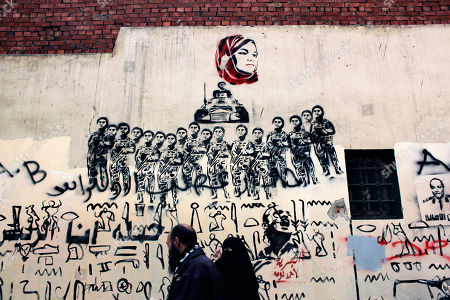 "An Egyptian couple walks under a mural depicting female activist Samira Ibrahim, who was forced to undergo a ""virginity test"" while in detention by the military, in Cairo, Egypt. After Egypt's ruling military sealed off streets around Cairo's Tahrir Square with walls of imposing concrete blocks, a group of artists decided to reopen the avenues on their own, in the public imagination, at least"